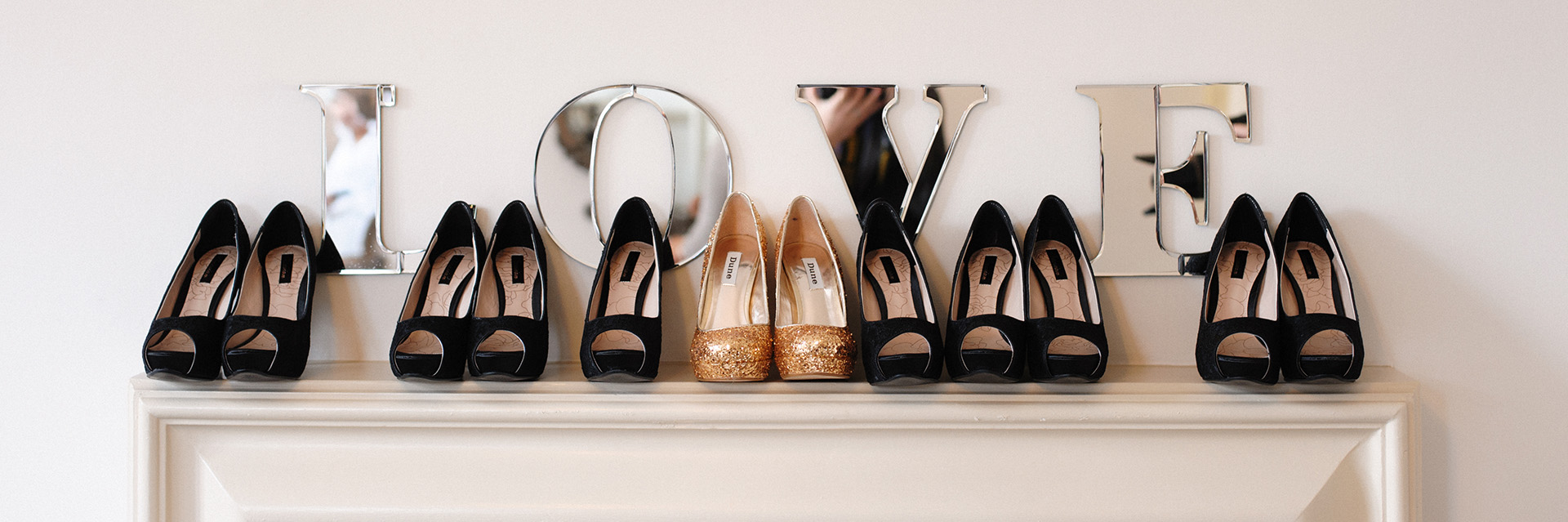 row of women's shoes on a mantlepiece