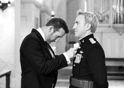 bestman-adjusts-grooms-buttonhole