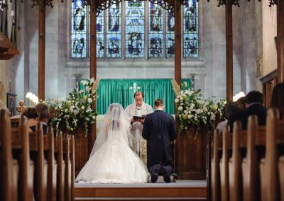 bride-and-groom-kneel-in-church-wedding