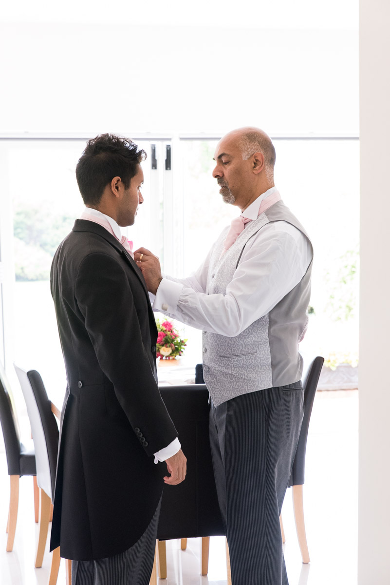 father adjusts groom's tie