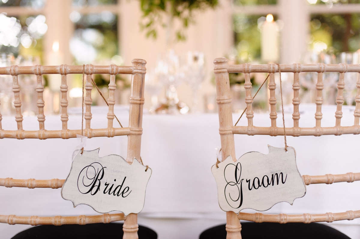 bride and groom signs hanging on decorative chairs
