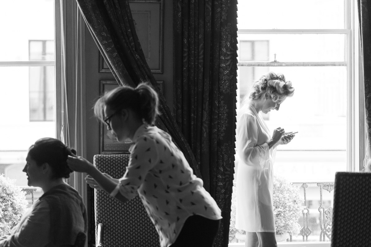 bride-to-be stands in window using phone during bridal preparation