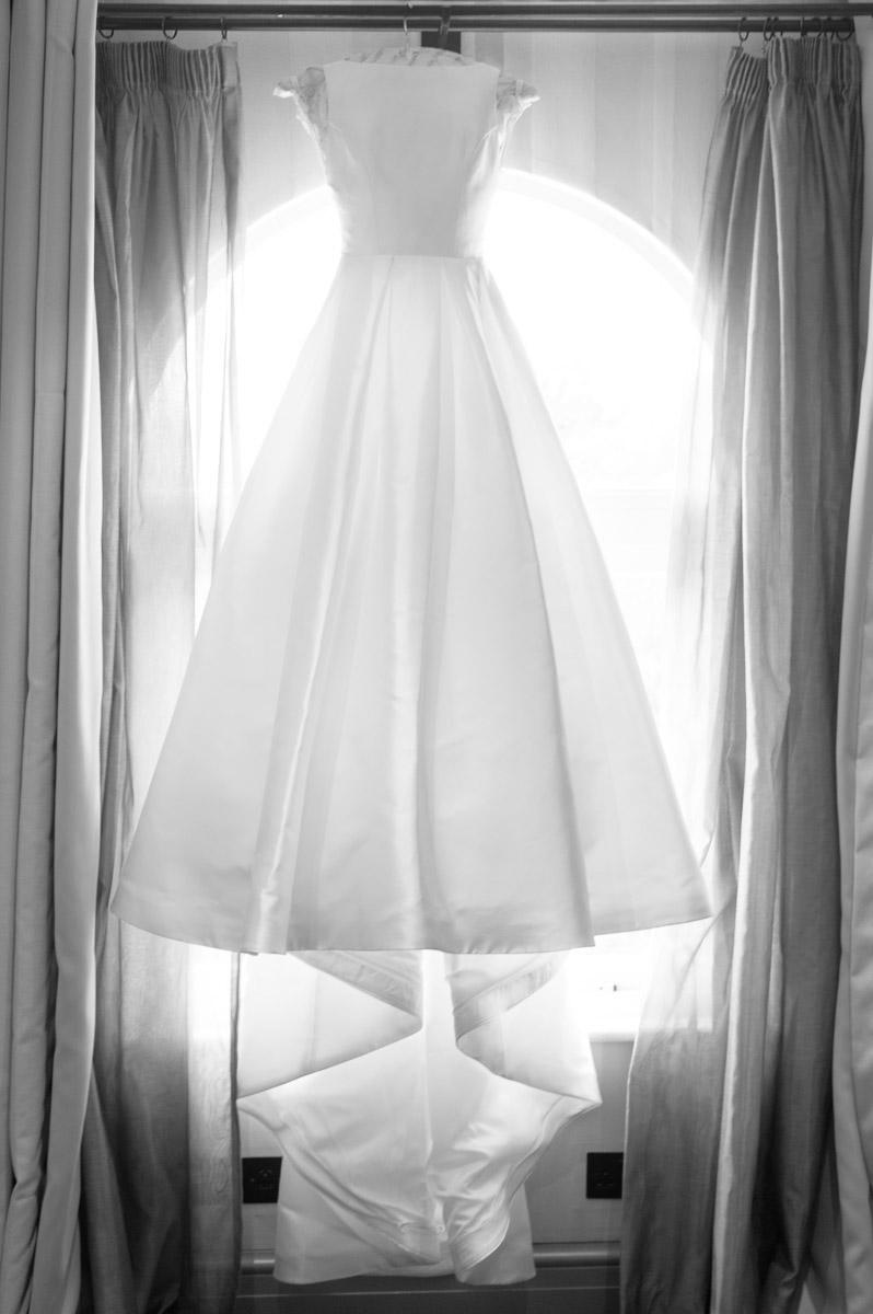 wedding dress hangs in window during bridal preparation