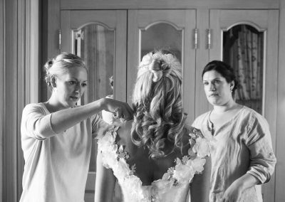 women-help-bride-wedding-dress