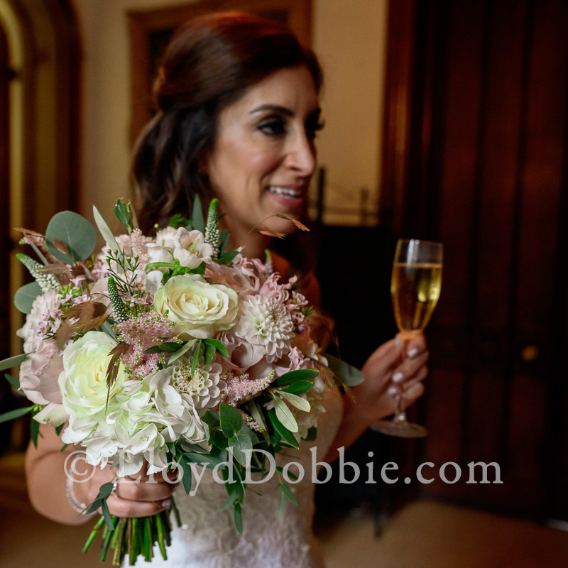 bride holds her bouquet and a glass of champagne