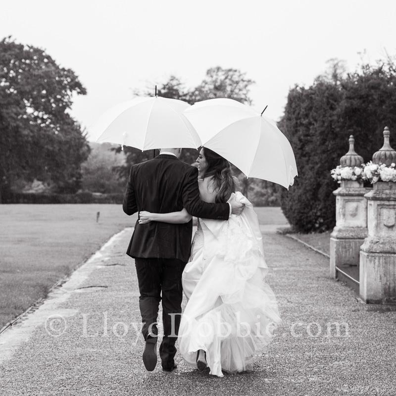 bride and groom walking away carrying umbrellas