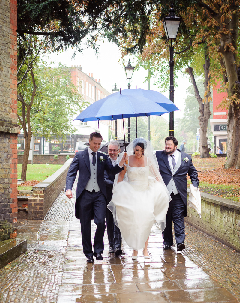 bridal party arrives for ceremony sheltering under umbrellas