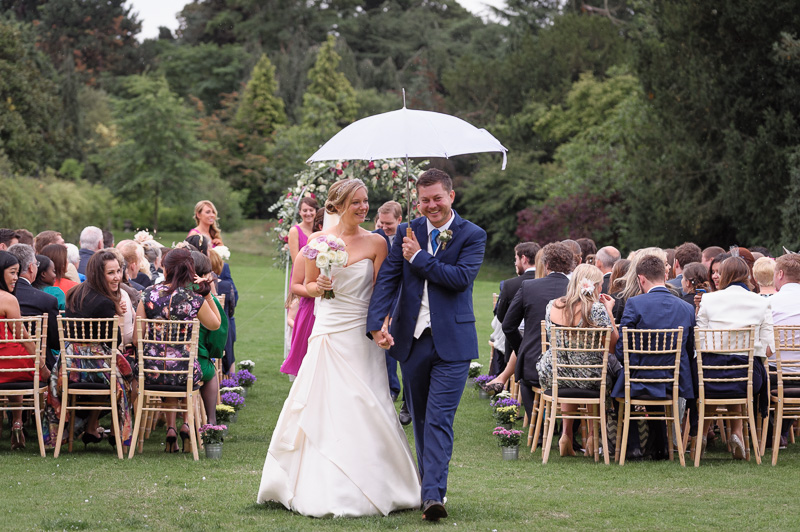 bride and groom leave wedding ceremony under umbrella