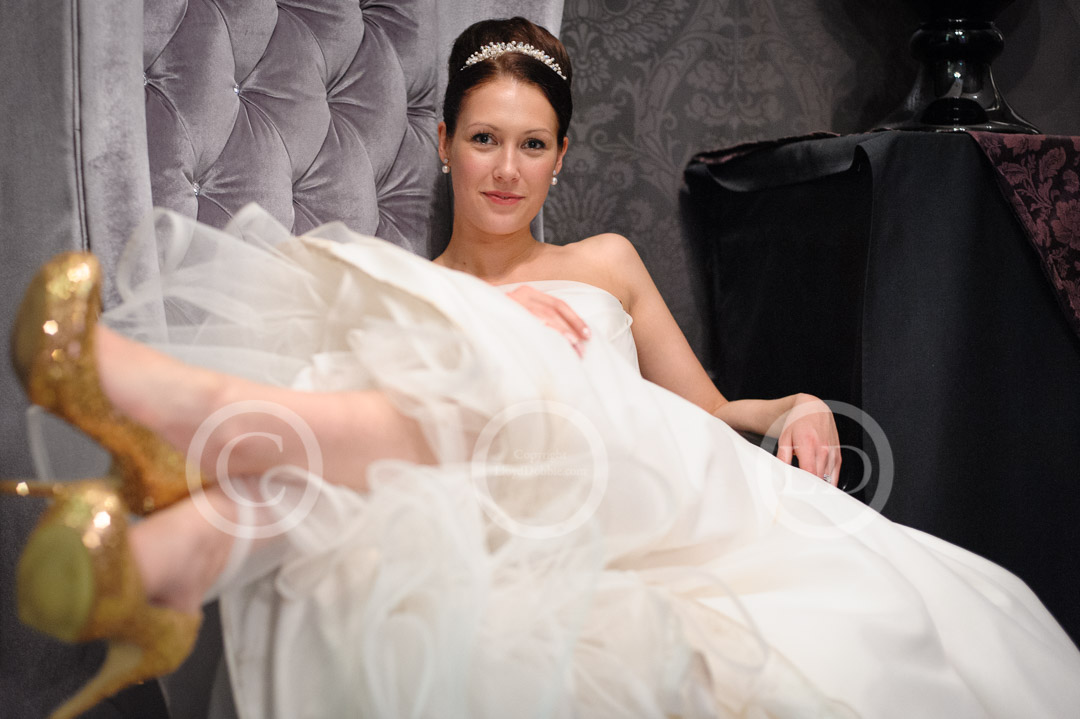 bride reclines in chair showing gold shoes