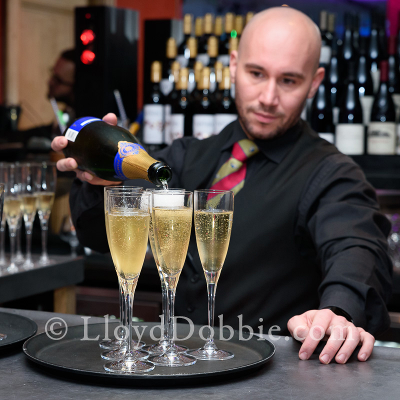 barman pours champagne at the Croc